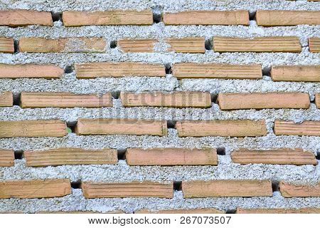 Ra Row Of Red Bricks With Blowholes And Rough Concrete Of A Strong Wall For Background Texture