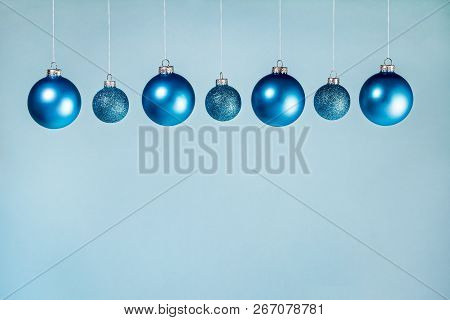 Row Of Seven Blue Christmas Ornaments Hanging With String