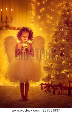Christmas Angel Child With Wings Hold Lighting Candle Front Of Xmas Tree, New Year Night