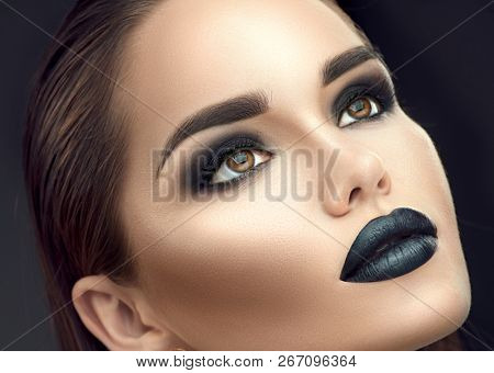 High Fashion Model Girl Portrait with Trendy gothic Black make-up. Young woman with black lipstick, dark smokey eyes, face contouring, beauty eyebrows. Perfect Smoky eyes makeup. Beautiful skin
