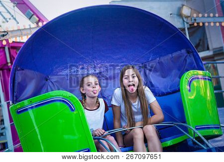Two cute teen girls playing and having fun while riding an amusement park ride. Sticking out their tongues at pulling a funny face. Carefree and fun-loving teen girls at a carnival