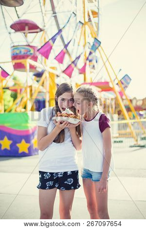 Two teen girls making a silly face while eating a funnel cake at an amusement park ride. Sticking out their tongues at pulling a funny face. Carefree and fun-loving teen girls at a carnival