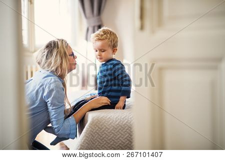 A Young Mother Talking To Her Toddler Son Inside In A Bedroom.