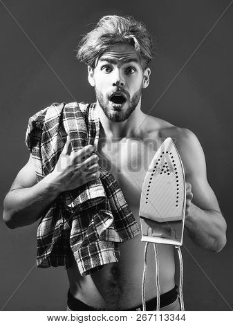Young surprised handsome topless man with messy hair with white iron, and plaid shirt over shoulder in beige pants in front of dark background poster