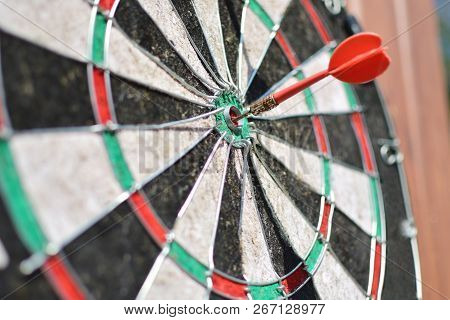 Old Dart Board With Aged Arrow Hitting A Target. Pursuing A Goal Concept.