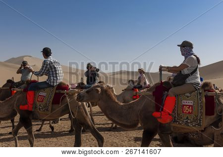 Dunhuang, China - August 8, 2012: Group Of Chinese Tourists Riding Camels At The Echoing Sand Mounta