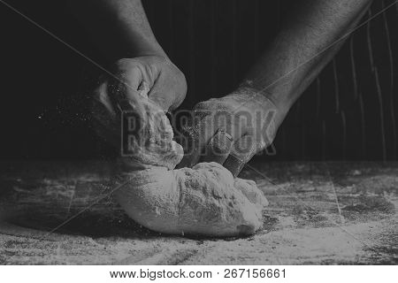 Man With Apron Kneading A Ball Of Dough On A Wooden Board By Hand In Artistic Conversion