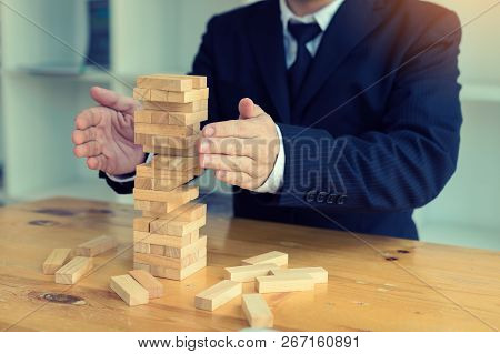 Hands Of Businessman Protect Block Wooden On Table With Risk Concept.
