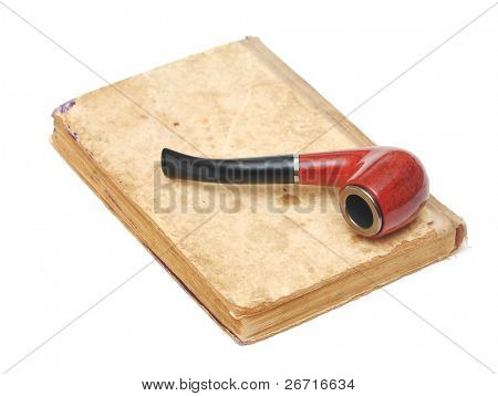 old book with vintage pipe on white