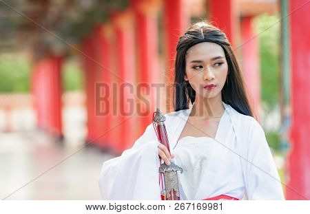 Beautiful Chinese Woman With A Traditional Suit With A Sharp Sword In Her Hands, Beautiful And Belli