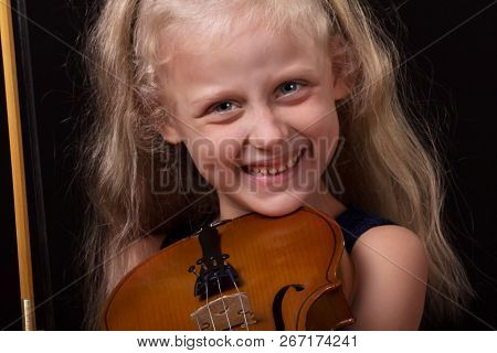 Learning To Play The Violin. Smiling Little Girl Holding A Violin In Hands On A Dark Background