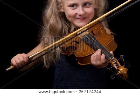 Blonde Little Girl Learning To Play The Violin Isolated On Black Background