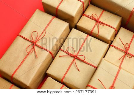 Gifts for friends and family. Heap of boxes. Selection of presents in handcrafted paper packaging and red twine bows. Delivery box poster