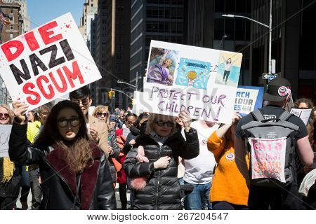 March For Our Lives: Women hold signs that say Die Nazi Scum and Protect Our Children on them during the march to end gun violence on 6th Ave, NEW YORK MAR 24 2018.
