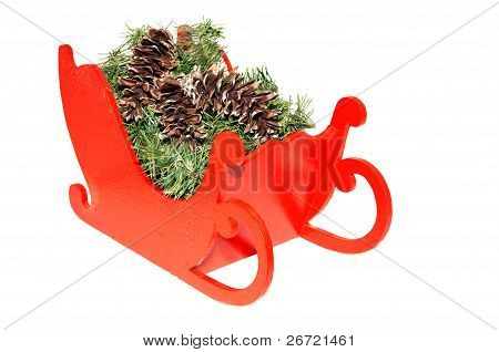 Wooden Toy Sleigh With Greens And Pinecones.