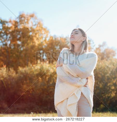 Happy smiling young girl hugging herself and enjoying nature on canted field. poster