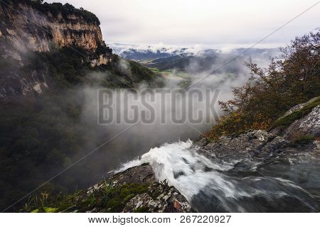 The Current Of A River Cascades Down The Stone Wall. In The Background You Can See The Fog In The Va