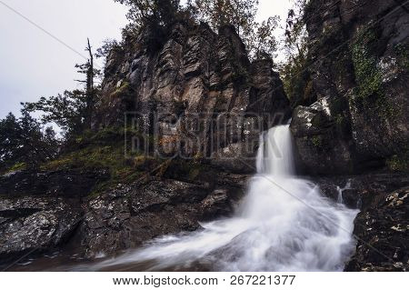 A Creek Falls Among The Rocks In Form Of Waterfall, The Leaves Of The Trees Already Have The First R