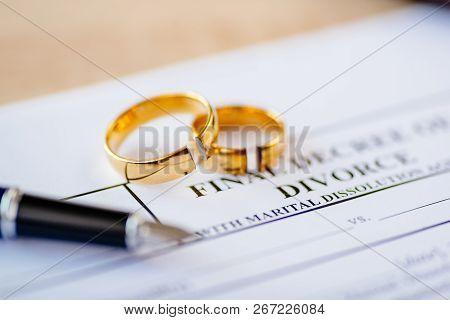 Broken Wedding Rings On Divorce Decree. Divorce, Separation And Family Law Concept