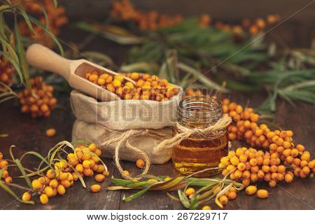Natural, Organic Sea-buckthorn Berry In Linen Bag And Sea Buckthorn Oil In Glass Vintage Bottle On D