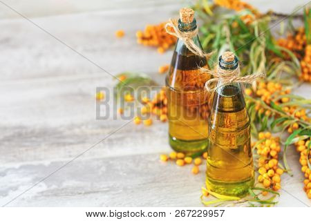 Natural Organic Sea-buckthorn Berry And Sea Buckthorn Oil In Glass Vintage Bottle On Gray Wooden Bac