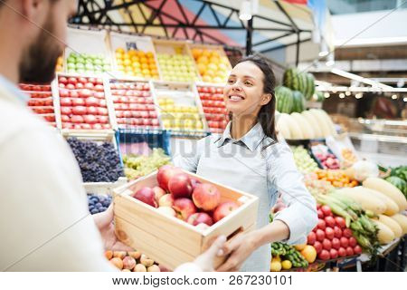 Cheerful content attractive young female grocer in apron giving box of apples to customer in farmers market, she working in organic food store
