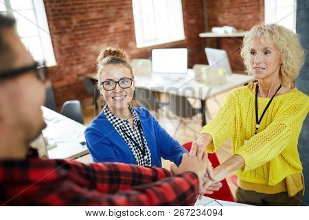 Two happy businesswomen and young man looking at each other while making pile of hands