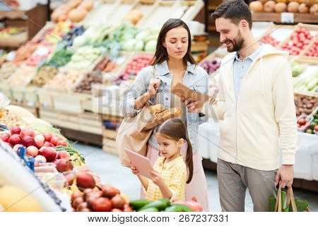 Content modern family in casual clothing buying fresh organic food in farmers market: concentrated parents reading shopping list while daughter using tablet