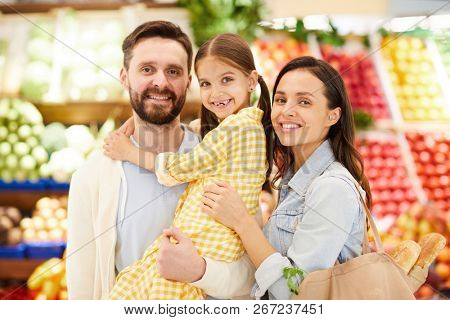 Cheerful friendly young family embracing and standing organic food store while looking at camera