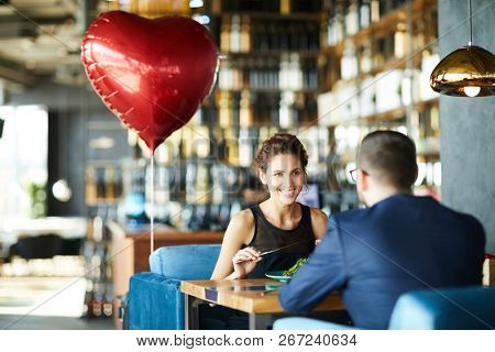 Happy young woman and her sweetheart enjoying lunch in restaurant on valentine day
