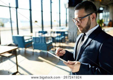 Bearded entrepreneur in formalwear browsing in the net while standing inside modern cafe