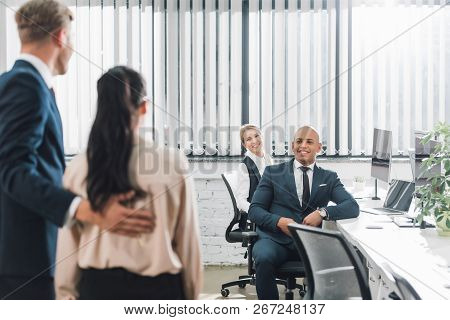 Back View Of Businessman Introducing New Colleague To Smiling Young Business People In Office
