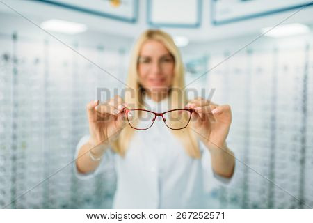 Female optician shows glasses in optics store