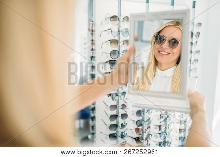 Female customer shooses sunglasses in optics store
