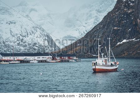 Ship fishing boat in Hamnoy fishing village on Lofoten Islands, Norway with red rorbu houses. With falling snow