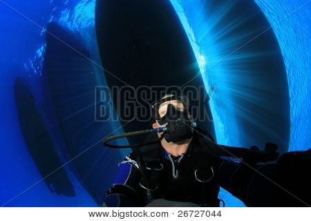 Scuba Diver under fleet of boats with sun rays