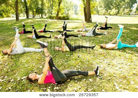 group stretching workout, large group stretches outdoor on a green grass  in park