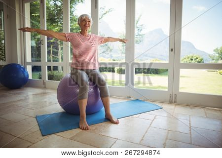 Senior woman performing stretching exercise on fitness ball at home