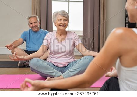 Senior couple with trainer sitting in lotus position meditating. Instructor with old man and elderly woman doing yoga at home. Fitness instructor helping old people keep fit.