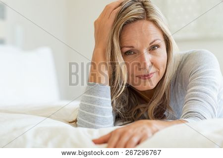 Thoughtful woman laying on bed in bedroom and looking at camera. Portrait of middle aged woman smiling. Portrait of a beautiful middle aged woman at home.