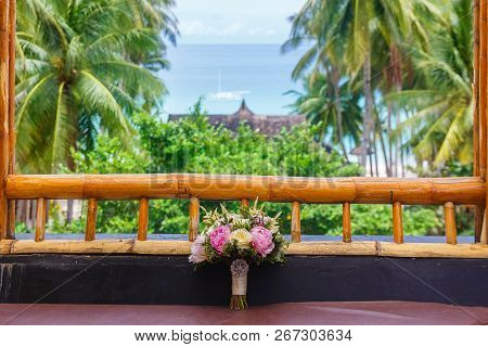 Wedding Accessories. Wedding Bridal Bouquet On The Window Of A Bamboo Hut. Tropical Landscape In The