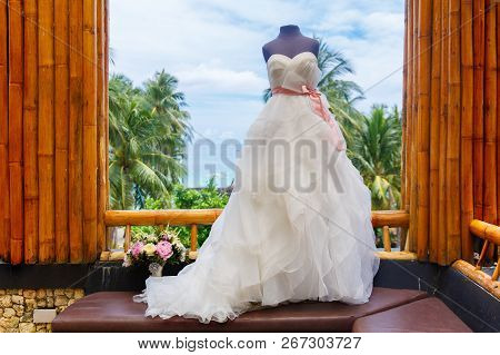 Wedding Accessories. Mannequin In A Wedding Dress, And A Bouquet Of The Bride On The Window Of A Bam