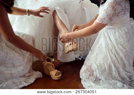 Wedding Preparations. Bridesmaid Helps To Wear Shoes On The Bride.