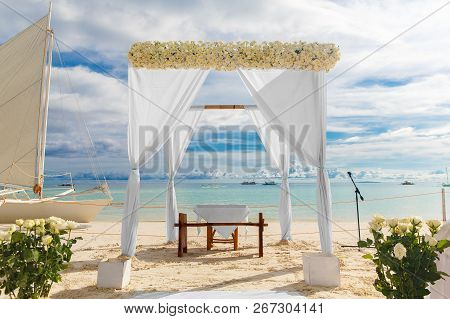 Wedding Ceremony On A Tropical Beach In White. Arch Decorated With Flowers On The Sandy Beach. Weddi