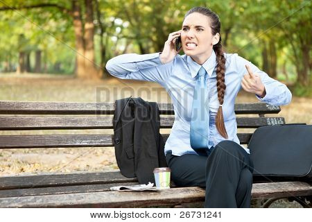 angry businesswoman  on mobile phone, facial expression with gestures ,  outdoor
