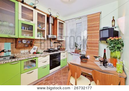 Green Kitchen interior with many utensils and window