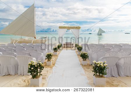 Wedding Ceremony On A Tropical Beach In White. The Arch Is Decorated With Flowers On The Sandy Beach
