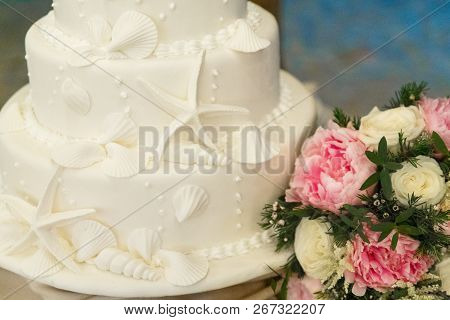 Wedding Cake Decorated With Shells And Starfish And The Bride's Bouquet.