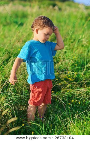 Little boy thinking hard standing on green grass lawn