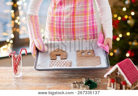 holidays, pastry and bakery concept - close up of woman holding oven tray with baked gingerbread house parts at home over christmas tree lights background
